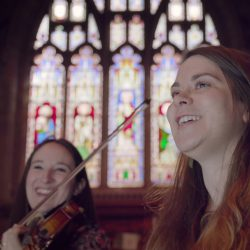 A violinist and singer in a church, with a large stained glass window in the background.