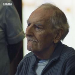 An elderly man looks sad.