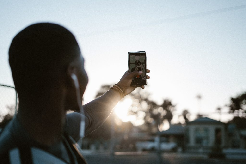 A man records a social media video on his mobile phone, in selfie mode
