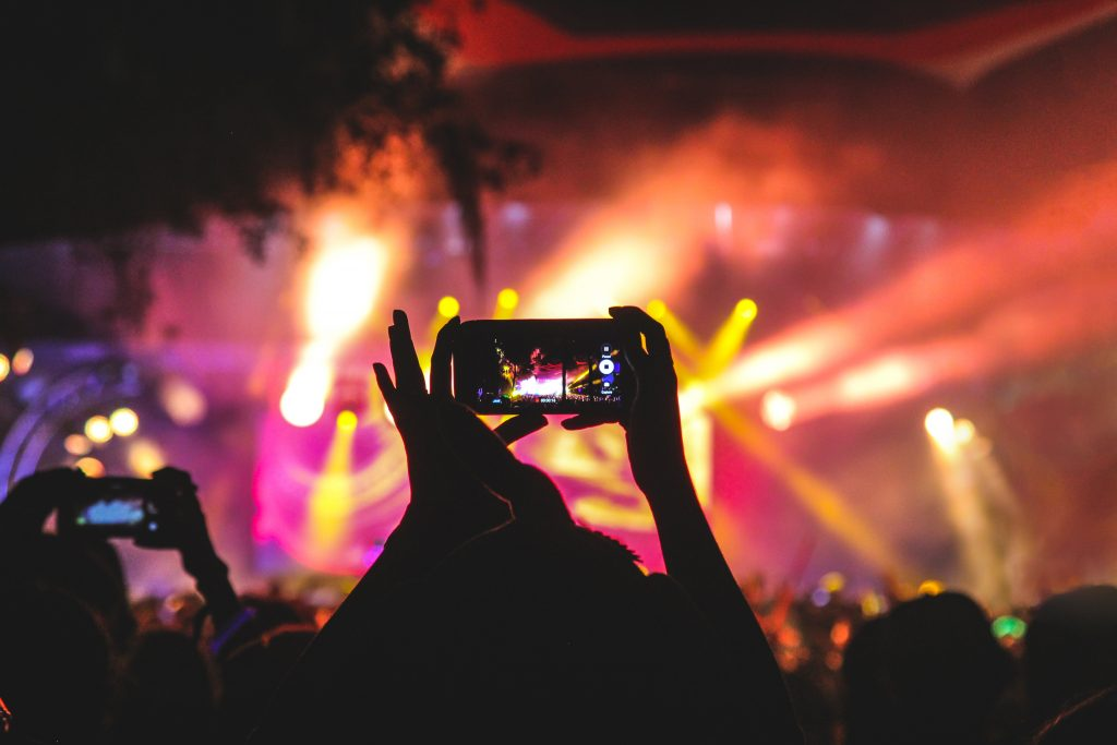 Somebody at a music concert filming social media video content on their phone.