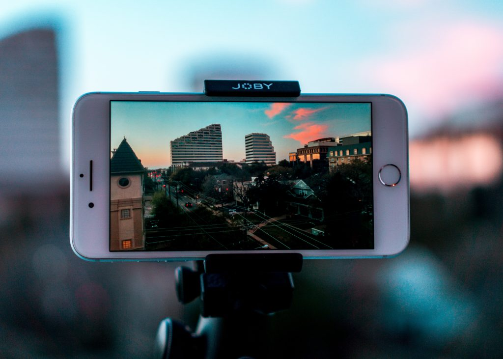 A phone on a tripod, filming video content of a city skyline