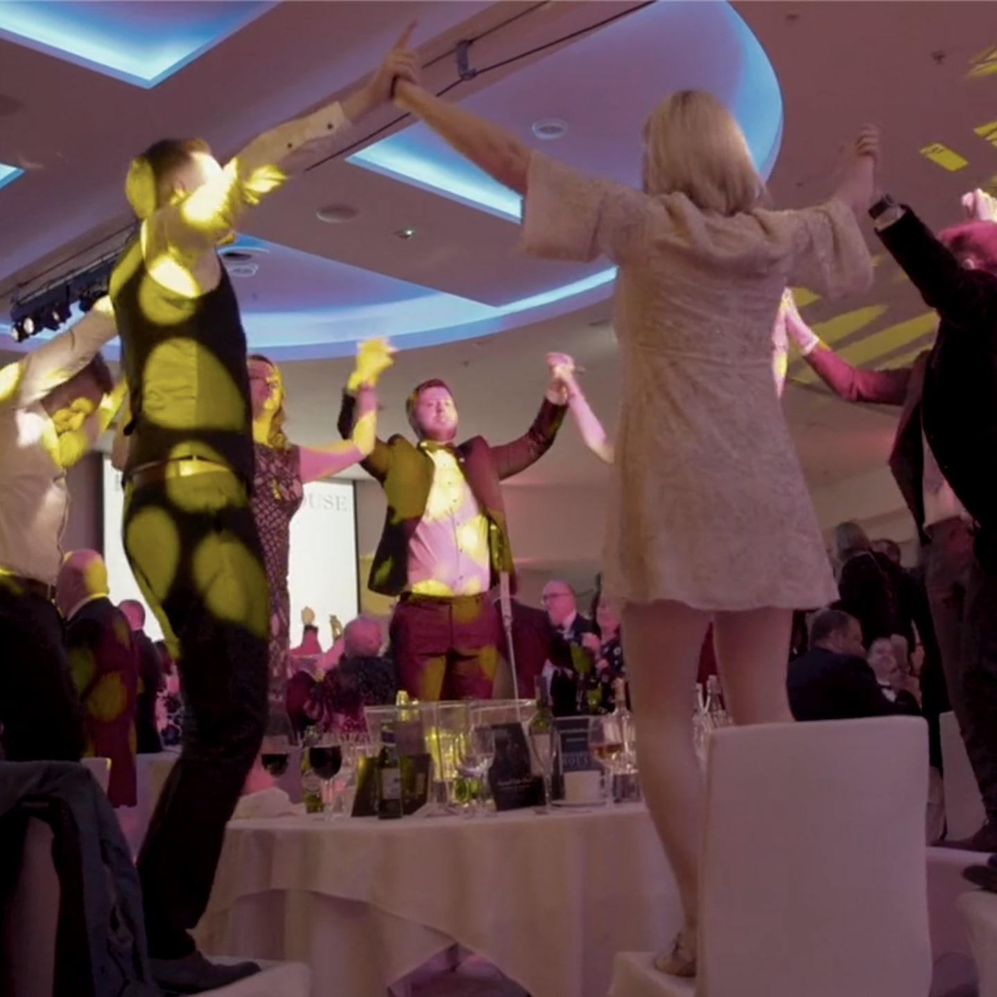 People standing on chairs, dancing