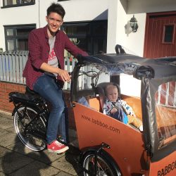 Ben Horrigan riding a cargo bike with a baby in it