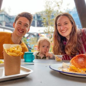 Ben and Ellie Horrigan, founders of video production company Studio 91 Media, eating food in Manchester with their child