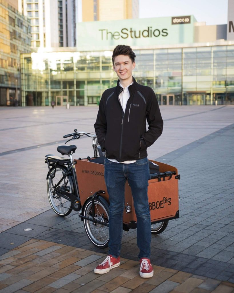 Ben Horrigan standing with Studio 91's cargo bike. The bike is full of video production equipment.