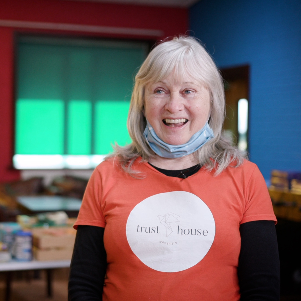 A woman smiling in a community centre, wearing a t-shirt with the Trust House logo
