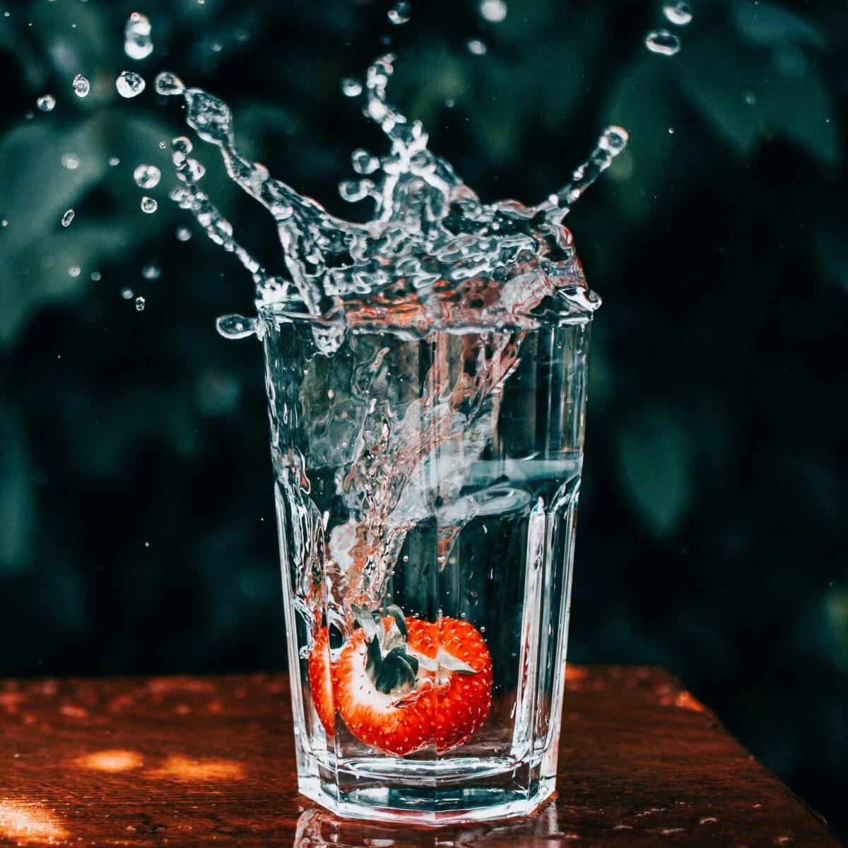 Detailed photo of a strawberry splashing into a glass